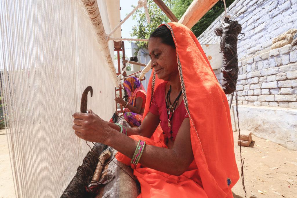 a woman weaving a rug